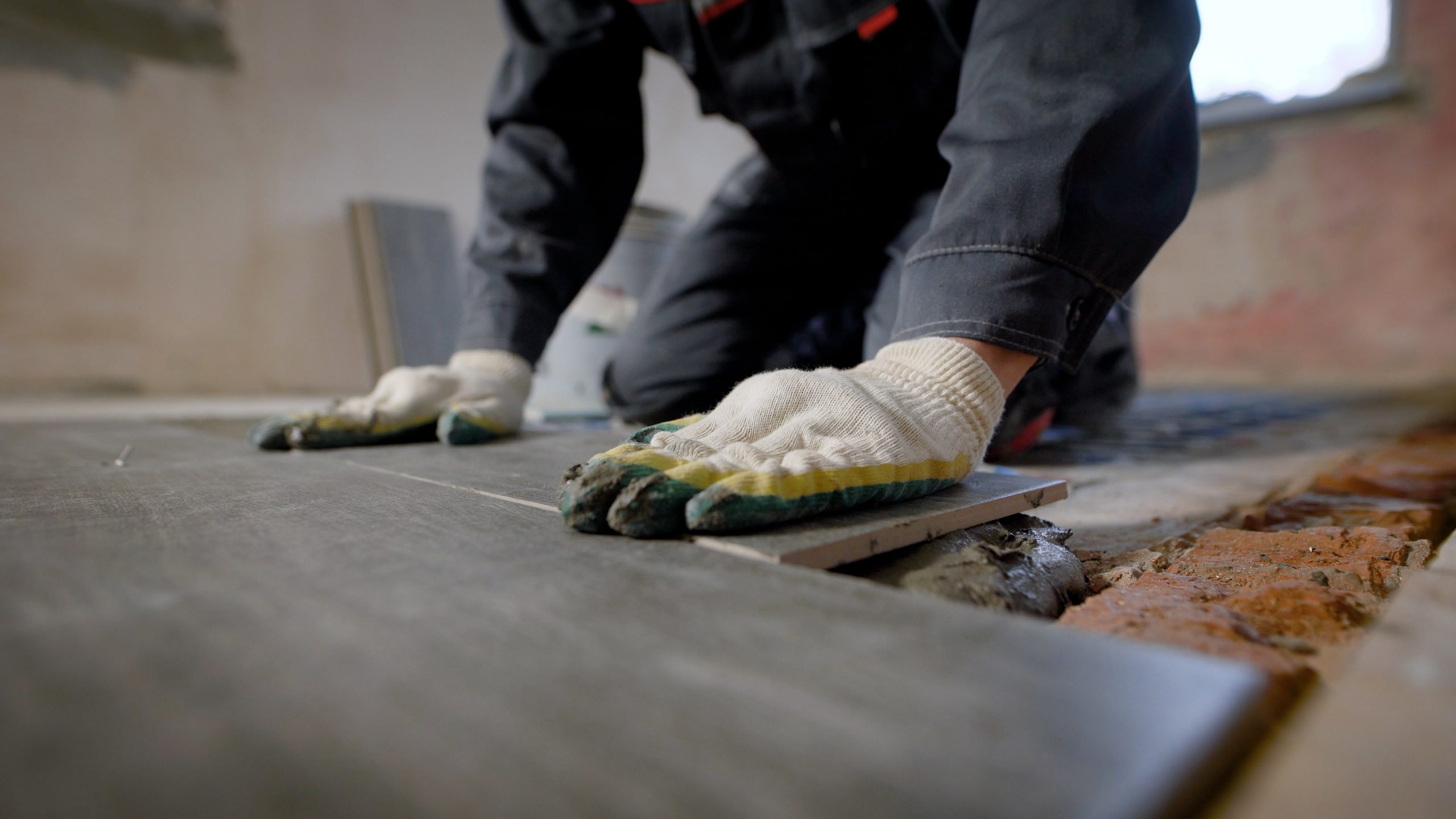 blog image of a contractor installing floor tile in an apartment
