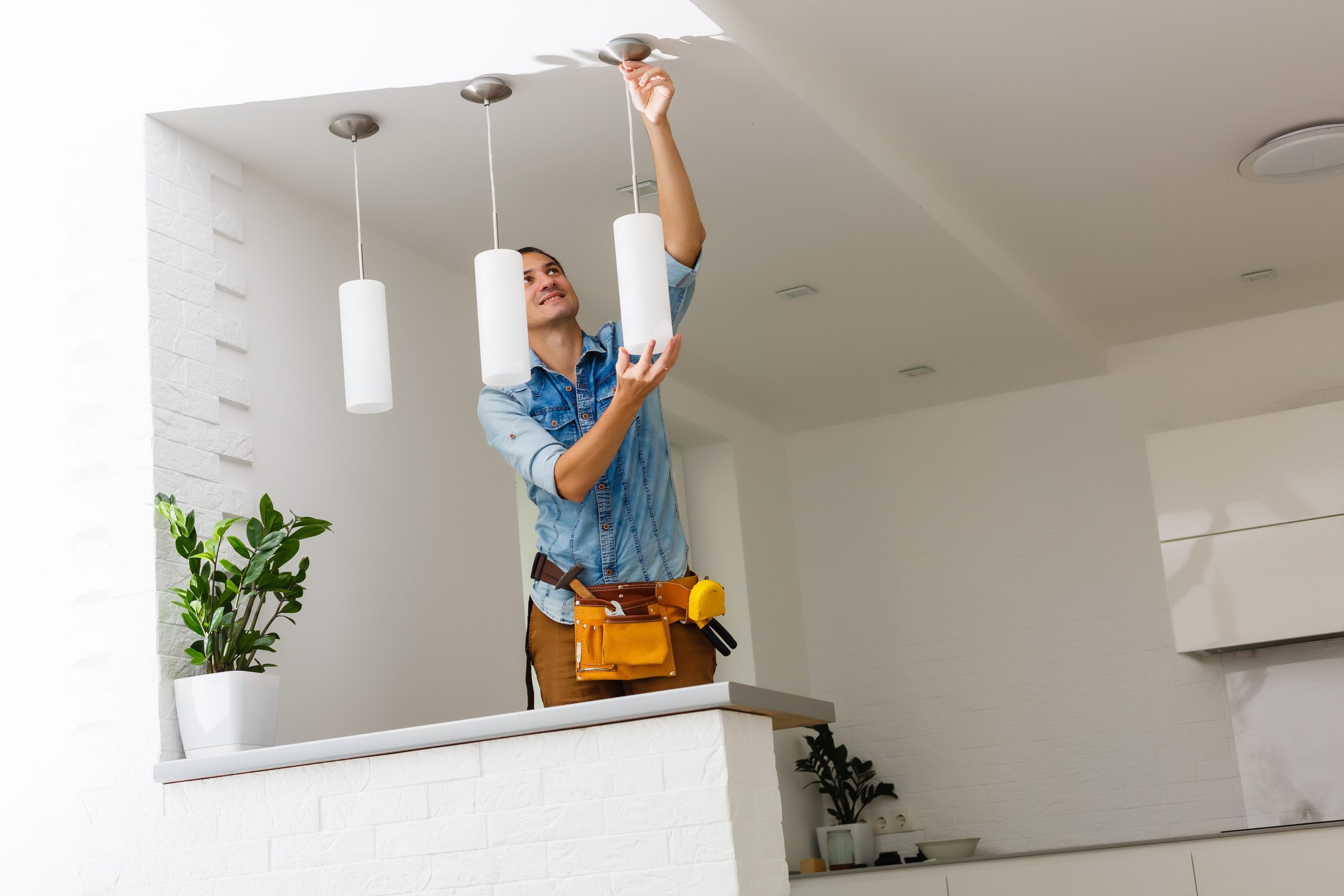 image of worker installing pendant lighting in apartment kitchen